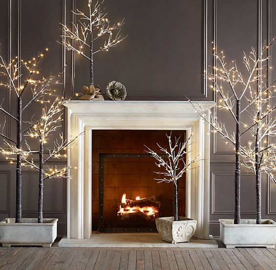 Beyaz şömineyi sade bir şekilde bırakarak etrafına led aydınlatmalarla kaplanmış ağaçlarla dekor edebiliriz.