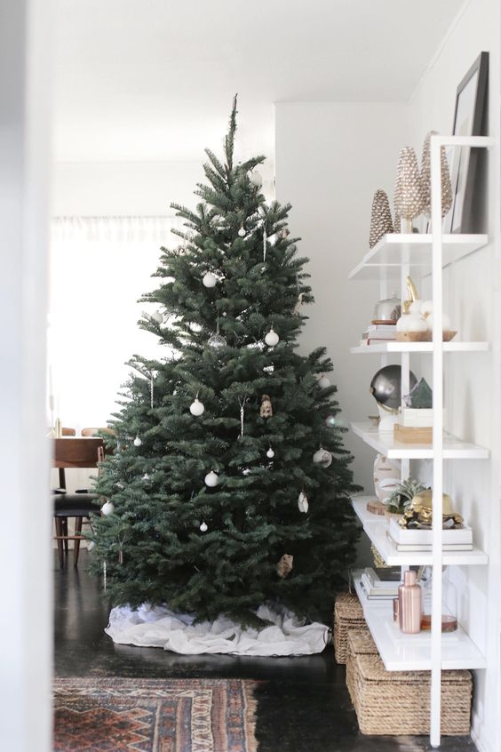 Beyaz noel süsleri ve sade büyük bir ağaçla evinizin sadeliğini koruyacak noel dekor fikri.